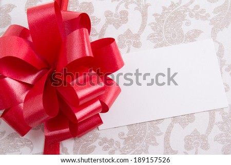 close up of gift box with big red bow and empty greeting card