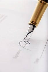 Close-up of gilded fountain pen signing contract, document. Vertical image.