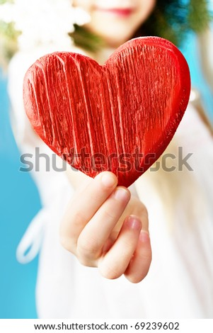 Close-up of girl holding wooden a red heart