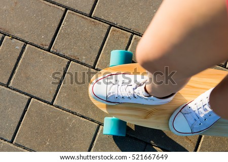 Close up of girl in white sneakers ready to extreme funny ride her skate longboard skateboard in sun light. Modern urban hipster girl have fun. Good sunny summer day for skateboarding. View from top.