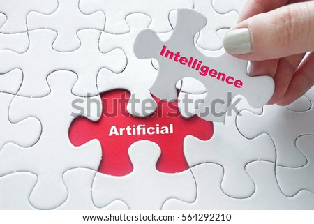 Close up of girl's hand placing the last jigsaw puzzle piece with word Artificial Intelligence #564292210