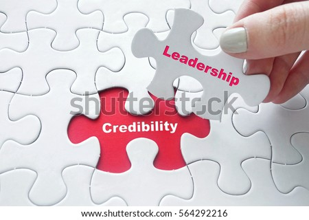 Close up of girl's hand placing the last jigsaw puzzle piece with word Credibility and Leadership #564292216
