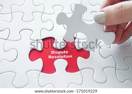 Close up of girl's hand placing the last jigsaw puzzle piece with word Dispute Resolution