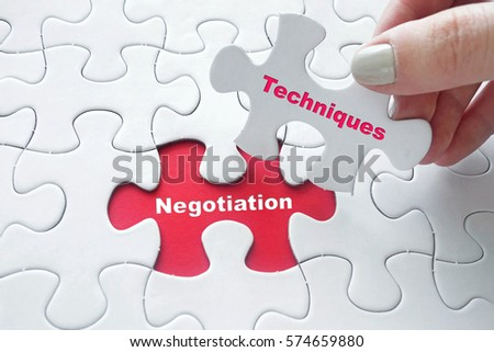 Close up of girl's hand placing the last jigsaw puzzle piece with word Negotiation Techniques #574659880