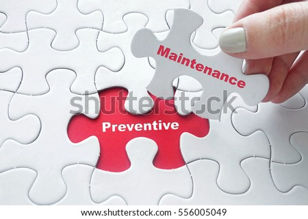 Close up of girl's hand placing the last jigsaw puzzle piece with word Preventive Maintenance #556005049