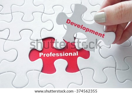 Close up of girl's hand placing the last jigsaw puzzle piece with word Professional Development as studying concept #374562355