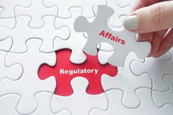 Close up of girl's hand placing the last jigsaw puzzle piece with word Regulatory Affairs