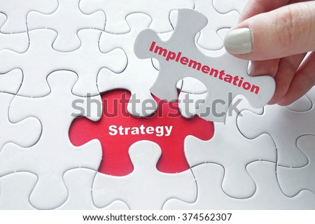 Close up of girl\'s hand placing the last jigsaw puzzle piece with word Strategy Implementation as business concept