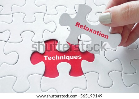 Close up of girl's hand placing the last jigsaw puzzle piece with word Techniques and Relaxation #565199149