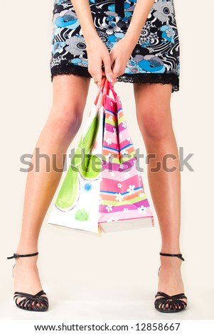 Close-up of girl's legs with paper bags in her hands on white background
