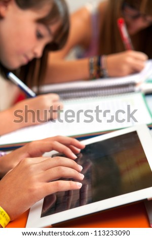 Close up of girls hands typing on tablet at homework session.