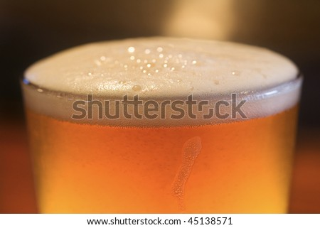 Close-up of glass of beer with foam on top. Vertical shot.