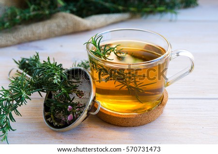 Close up of glass of rosemary herb tea, bunch of fresh rosemary and vintage tea infuser on wooden background.  Rustic style.  ストックフォト ©