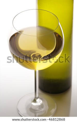 Close-up of glass of white wine and bottle in back light on light background.