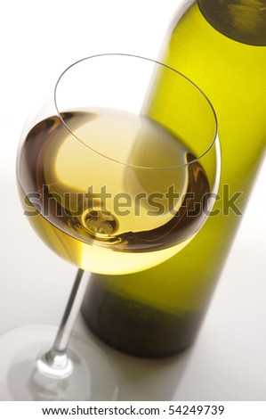 Close-up of glass of white wine and bottle in back light on light background. - stock photo
