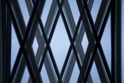 Close-up of glass wall with X-shape metal framework. Hitech office building exterior or interior fragment. Abstract modern architecture background. Geometric structures of parallel girders.