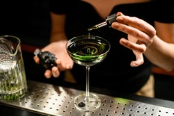 close-up of glass with bright green drink in which female bartender's hand adds ingredient using dropper