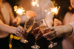 Close-up of glasses of clinking Champagne with Bengali lights. Celebration concept