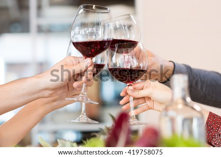 Close up of glasses raising a toast at lunch. Closeup of friends toasting glasses of red wine in a party. Group of friends a toast to the cheers of red wine at restaurant. #419758075