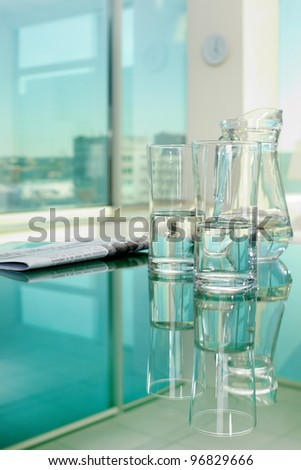 Close-up of glassware and newspaper on table
