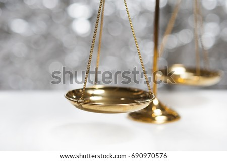 Close up of gold brass balance scale, Sign of justice isolated on bokeh background