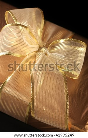 Close-up of gold foil gift with gold translucent bow on black background.