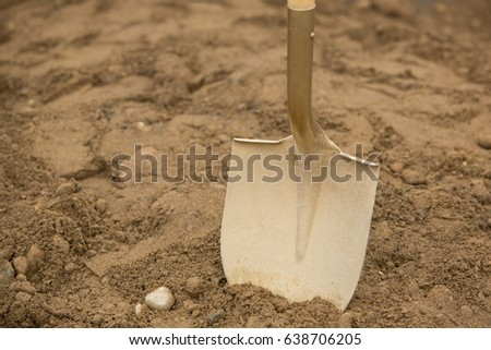 Close up of gold painted shovel head dug into sand and rock dirt at ceremonial ground breaking event for commercial and residential building development #638706205
