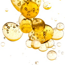 Close up of golden bubbles on illuminated background