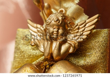 close-up of golden cherub figure with two jingle bells. Elegant christmas decoration with Smiling cherub copper colored and two jingle bells on brown background. Cherub for Christmas tree on canvas
