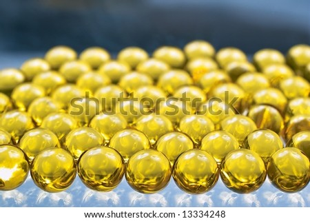 Close up of golden colored oil capsules