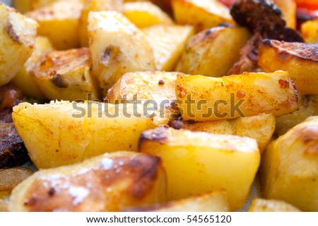 Close up of golden crisp roasted potatoes with mushrooms.
