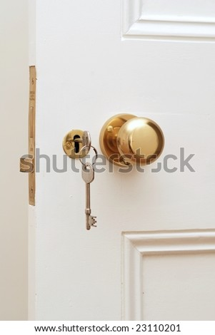 Close up of golden key at white door
