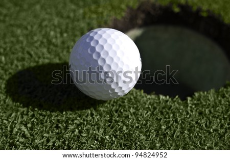 Close up of golf ball at the edge of the hole in the putting green.