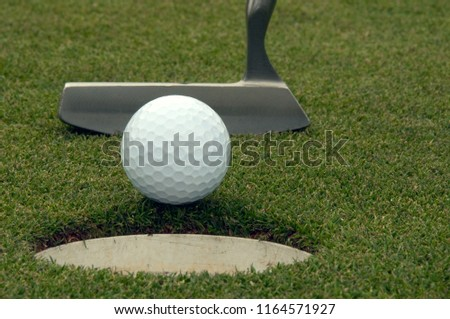 Close-up  of golf ball entering the cup with the putter in the background