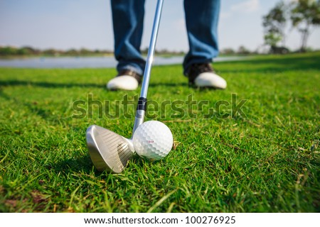 Close up of golf ball on green grass with the driver positioned ready to hit the ball