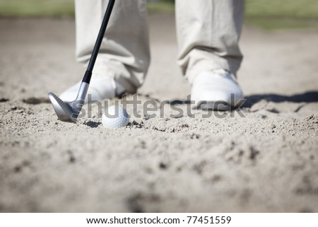 Close up of golf player pitching ball in bunker.