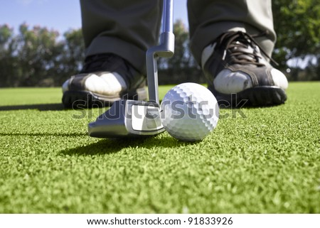 Close up of golfer setting up for a putt on the putting green.