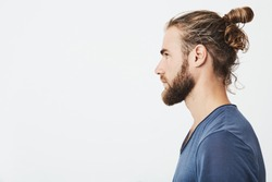 Close up of good-looking bearded hipster guy with hair in bun, in blue t-shirt standing in profile, looking aside, posing for photo.