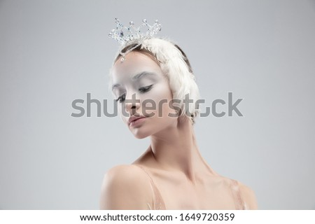 Close up of graceful classic ballerina on white studio background. Woman in tender clothes like a white swan character. The grace, artist, movement, action and motion concept. Looks weightless. Foto stock ©