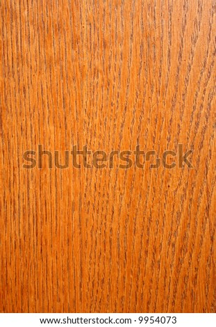 Close up of grain pattern on an orange stained wood board.