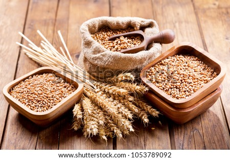 close up of grains and wheat ears on a wooden table