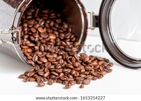 close up of grains of black coffee inside a coffee bottle isolated on white background with copy space.