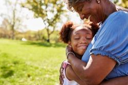 Close Up Of Granddaughter Hugging Grandmother In Park