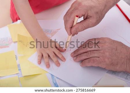 Close-up of grandpa drawing little boy hand