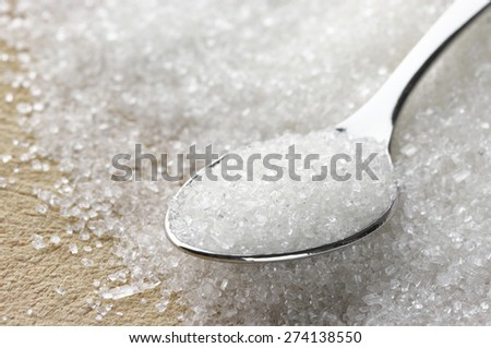 Close-up of granulated sugar in spoon and sugar pile. Shallow DOF.