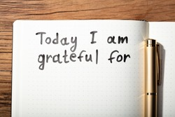 Close-up Of Gratitude Word With Pen On Notebook Over Wooden Desk
