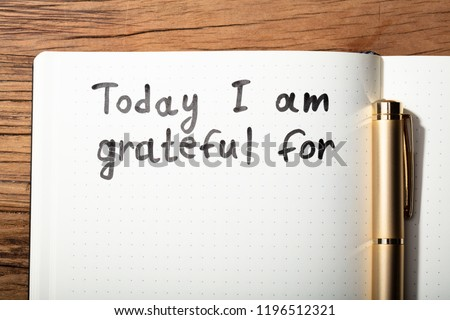 Close-up Of Gratitude Word With Pen On Notebook Over Wooden Desk Stockfoto ©