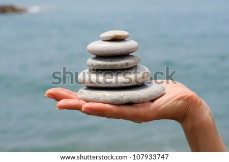 Close-up of gravel pile in woman's hands with sea background