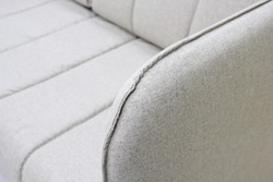 Close-up of gray sofa with armrest. Textiles, new furniture modern design. With free space for text.