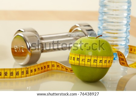 Close?up of green apple with measuring tape and two metal barbells on background - stock photo